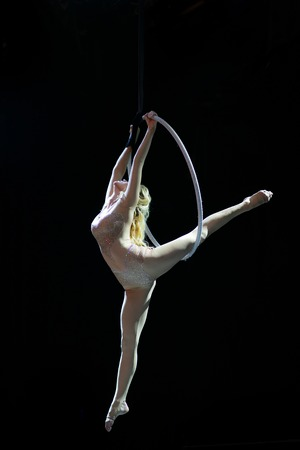Graceful aerial acrobat doing her performance with a hoop isolated on black