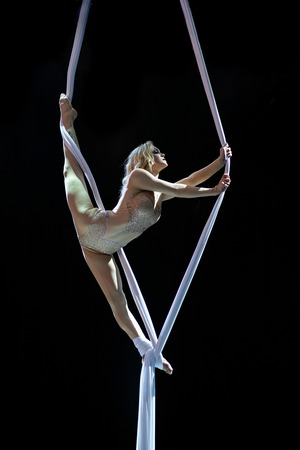 Blond aerial performer with white aerial silks isolated on black background