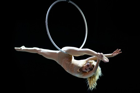 Graceful aerial acrobat doing her performance with a hoop isolated on black Stock Photo