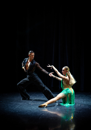 Paar Tänzer, die auf isoliertem schwarzem Hintergrund auftreten