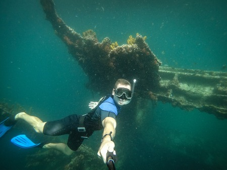 Free diver taking selfie with sunken ship on background Stock Photo