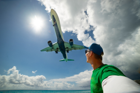 Slim girl on the beach wearing swimsuit with huge airplane flying over her head on Maho beach. Concept of travelling and perfect vacation and holiday