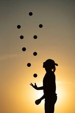 Silhouette d'un homme jonglant avec des balles au coucher du soleil
