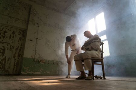 A crazy man in a straitjacket is tied to a chair in an abandoned old clinic and the other insane man coming closer with interest