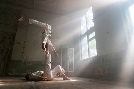 Male duo making acrobatic tricks wearing costume of insane people in abandoned room with sun rays from windows 스톡 콘텐츠