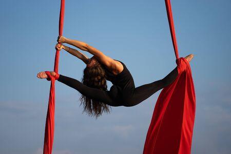 Belle et flexible artiste de cirque féminine dansant avec de la soie aérienne sur fond de ciel Banque d'images