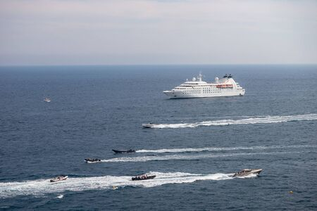 Passenger cruise ship at sea during sunny day surrounded by lots of powerboats. Monte Carlo, Monaco.