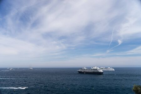 Two cruise ships at sea during sunny day surrounded by lots of powerboats. Monte Carlo, Monaco.
