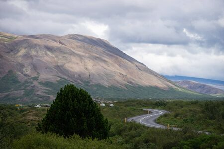 S-curve road near hill with Green tree and sky in Iceland Stock fotó