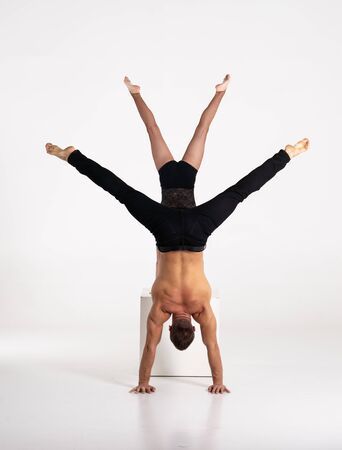 Good shaped man and woman practicing handstand exercise isolated on white background. Strength and motivation.