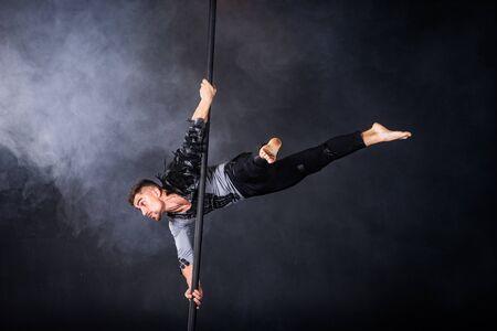 Leistungskonzept. Mann, der an chinesischer Stange hängt. Athlet, der fliegende Stange durchführt