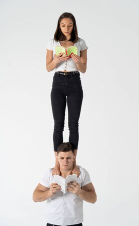 Creative composition of woman standing on mans shoulders and reading book. Concept of education and self-improvement Banco de Imagens