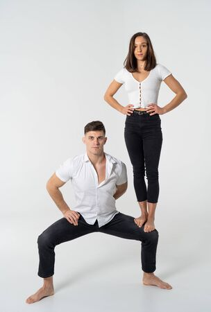 Concept of dominant women on man in relation ship. Woman standing on the man knee with white background
