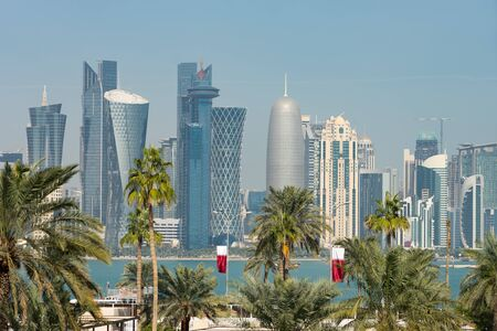 Panoramic view of modern skyline of Doha through blurred palm trees. Qatar on sunny day.