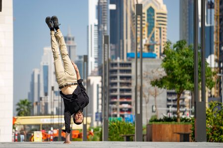 Acrobat keep balance one the hands with blurred Dubai cityscape. Concept of modern, business and unlimited possibility.