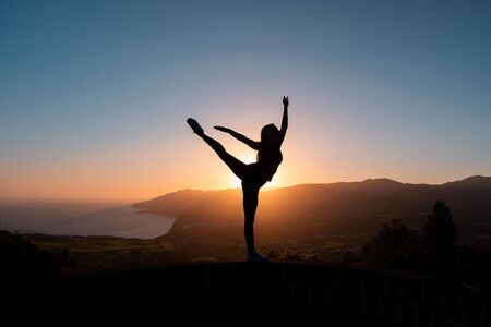 Silhouette of woman enjoying freedom feeling happy at sunset with mountains and sea on background.