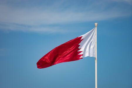 Elegant Qatar flag flying in the sky on a bright sunny day.