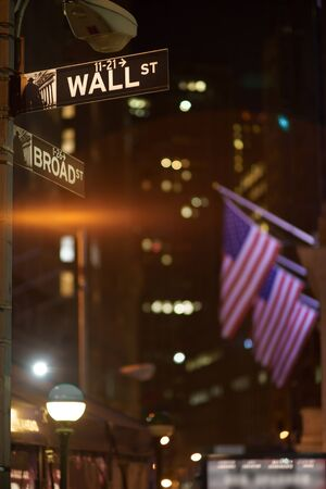 Broadway and Wall Street Signs at the night with US flags on background, Manhattan, New York
