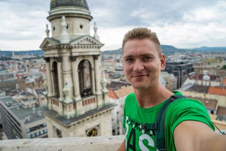 young attractive guy with blue eyes taking selfie on the top view point with Budapest on background Stok Fotoğraf
