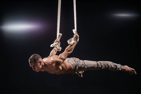 circus artist on the aerial straps with Strong muscles on black background