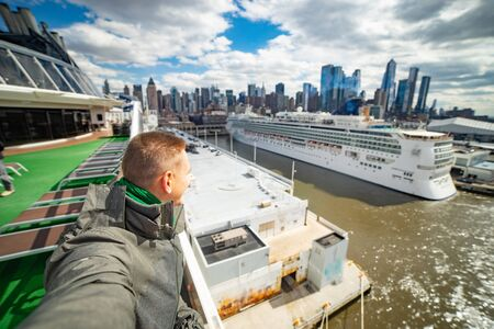 Young man makes selfie with huge cruise ship and New York city on background. Concept of happy vacation and travelling