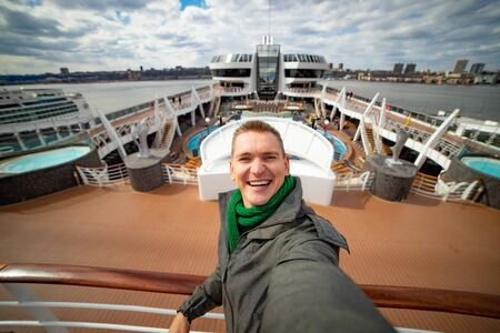 Young man makes selfie with huge cruise ship and city on background