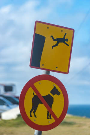 Icelandic sign no dogs and you can fall from cliff. Latrabjarg Фото со стока