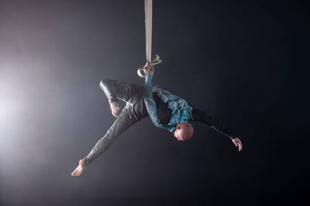 Circus artist on the aerial straps with costume on the black and smoked background.