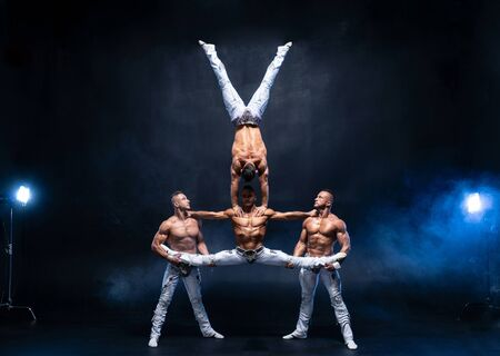 Four muscular man perform difficult acrobatic tricks on black studio.