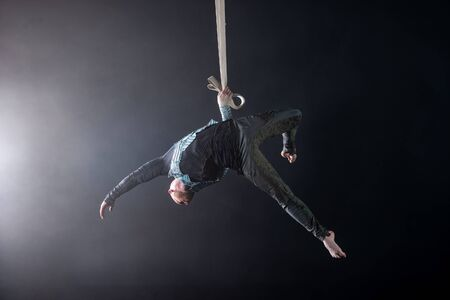 Circus artist on the aerial straps with costume on the black and smoked background. Stock Photo
