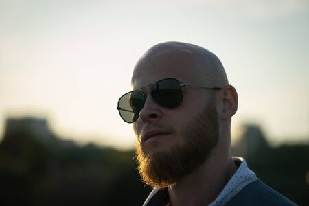 Bold Guy with a stylish beard and sunglasses on a sky background during sunset. Concept of success and will