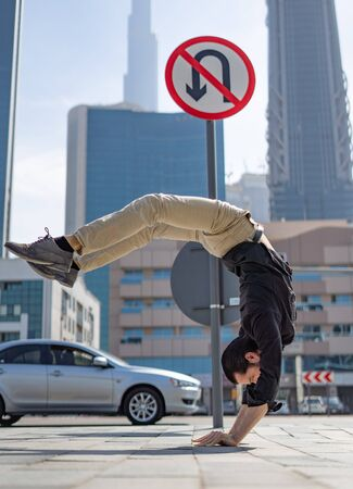 Flexible Acrobat keep balance on the hands with blurred Dubai cityscape and traffic sign U-Turn is prohibited. Concept of modern, business and unlimited possibility. Stock Photo
