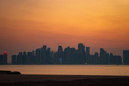 Vibrant Skyline of Doha at dramatick sunset as seen from the opposite side of the capital city bay