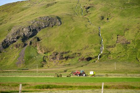 Red Tractor collecting stack of grass on green field with beautiful river going by the mountain on background