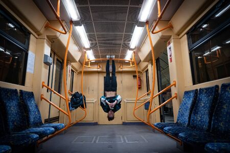Girl hanging by feet upside down in the subway carriage and using smartphone. Concept of overusing social networks and addiction.