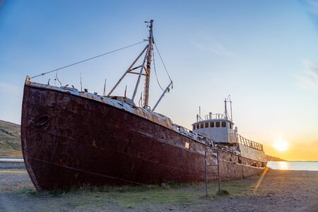 An out-of-the-way whaling ship that wrecked on the beach to Latrabjarg during sunset. Stock Photo