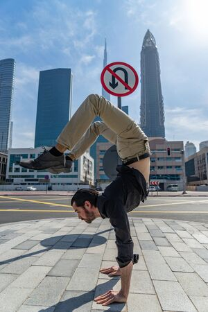 Flexible Acrobat keep balance on the hands with blurred Dubai cityscape and traffic sign U-Turn is prohibited. Concept of modern, business and unlimited possibility