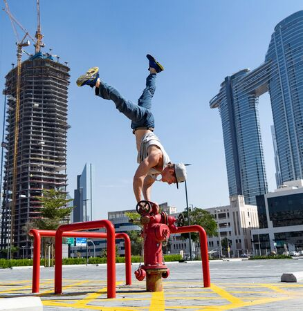 Flexible Acrobat keep balance with one hand on the fireman hydrant with blurred Dubai cityscape. Concept of modern and safety. Фото со стока