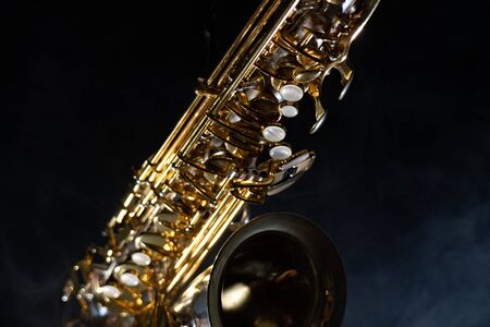 Golden shiny alto saxophone on black background with smoke. copy space Banque d'images