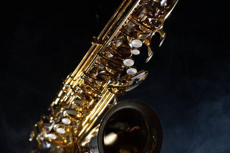 Golden shiny alto saxophone on black background with smoke. copy space 版權商用圖片