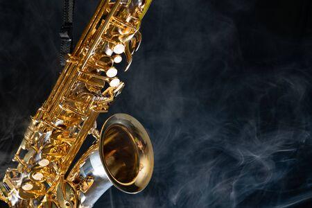 Golden shiny alto saxophone on black background with smoke. copy space