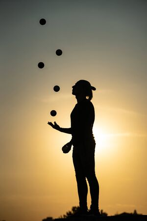 Silhouette of juggler with balls on colorful sunset