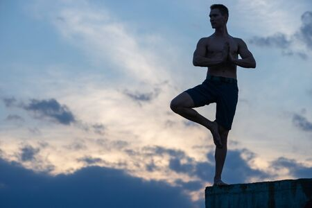 Fit young man practices sun salutation yoga on the edge of cliff at sunset