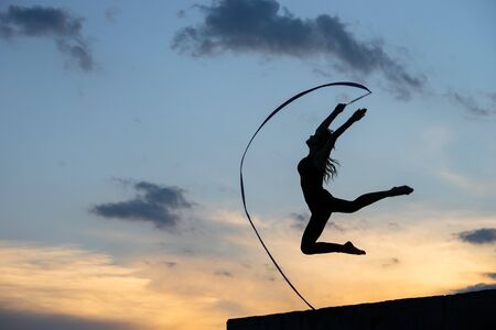 Professional gymnast woman dancer with ribbon on sky background