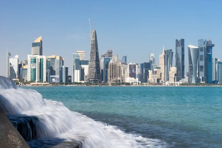 Panoramic view of modern skyline of Doha with small waterfall foreground. Qatar on sunny day