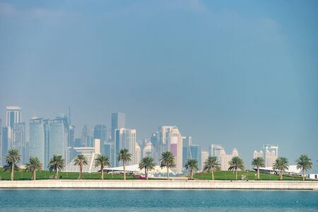 Panoramic view of modern skyline of Doha with Palms foreground. Concept of healthy environment