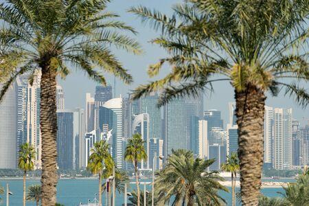 Panoramic view of modern skyline of Doha through blurred palm trees. Qatar on sunny day 写真素材
