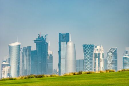 Panoramic view of modern skyline of Doha with green grass foreground. Concept of healthy environment 写真素材