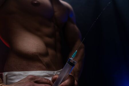 Bodybuilder holding big syringe with injection. concept of steroid in the sport and addiction