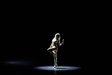 Silhouette of Beautiful good shaped blond woman singing on the stage with microphone